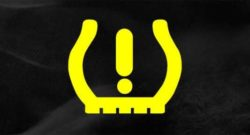 The tire pressure light blinking on the dashboard of a car.