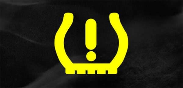 The tire pressure light blinking on the dashboard of a car